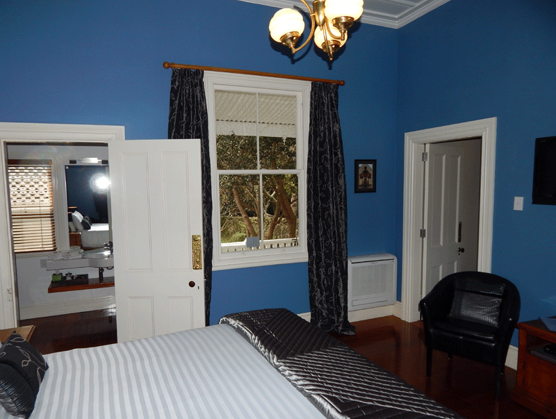 King-size bed and Flat Screen TV in the bedroom of the Blue Room Suite